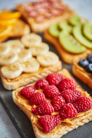 Six Healthy breakfast toasts. Wholegrain bread slices with peanut butter and various fruits. Served on grey cutting board. Top view, grey stone background. Dieting concept with cpoy space Фото со стока