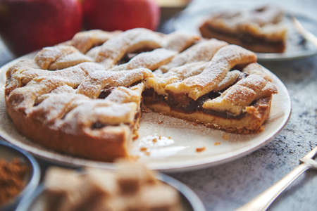 Fresh baked apple pie with cutted slice on small plate. With ingrediends on side. Fresh fruits, brown sugar cubes, cinnamon. Sprinkled with powder sugar. Stockfoto