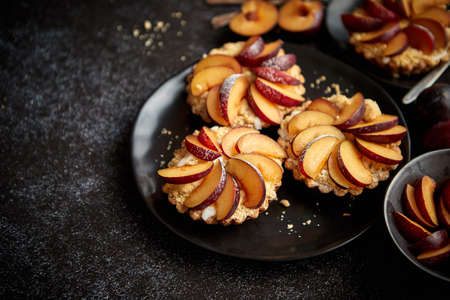 Delicious homemade mini tarts with fresh sliced plum fruit. Sprinkled with icing sugar. Placed on black ceramic plates with fresh pieces of plums on sides. Dark rusty background from top. Stock fotó