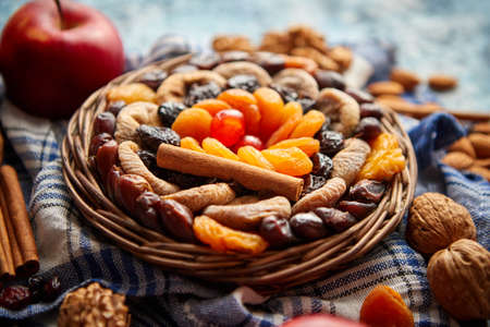 Composition of dried fruits and nuts in small wicker bowl placed on a stone table. Assortment contais almonds, walnuts, apricots, plums, figs, dates, cherries, peaches. Above view with copy space.