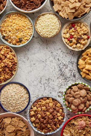 Assortment of various kinds cereals placed in ceramic bowls with cornflakes, granola, cereals and oatmeal. Flat lay, top view on white rusty table with copy space in the middle Stockfoto