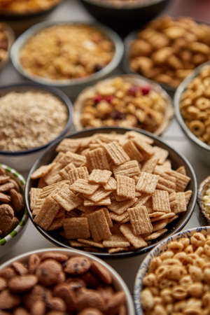 Close up and selective focus. Composition of different kinds cereals placed in ceramic bowls with cornflakes, granola, cereals and oatmeal. Flat lay, top view on white wooden table.