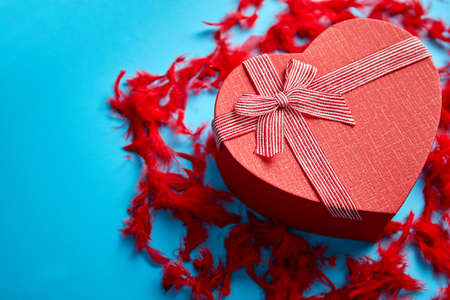 Red, heart shaped gift box placed on blue background among red feathers. Love or Valentine day romantic concept. Top view Imagens