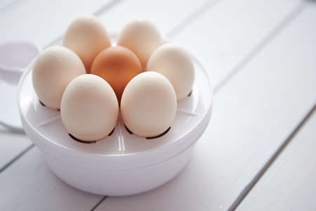 Chicken eggs in a egg electric cooker on a white wooden table ready for boiling.