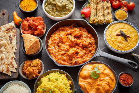Various Indian dishes on a table. Spicy chicken Tikka Masala in iron pan. Served with rice, naan and spices. Set of different kind Indian food.