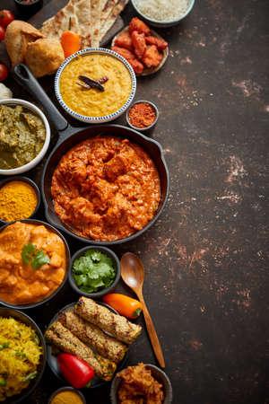 Auswahl an verschiedenen indischen Cousine auf dunklem rostigem Tisch. Chicken Tikka Masala, Butter, Nilgiri, Daal Tarka. Serviert mit gebratenem Reis, Naan-Brot und Gewürzen. Flache Lage mit Kopienraum.