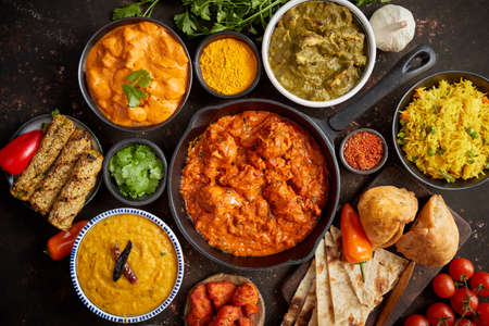 Assortment of various kinds of Indian cousine on dark rusty table. Chicken Tikka Masala, Butter, Nilgiri, Daal Tarka. Served with fried rice, naan bread and spices.