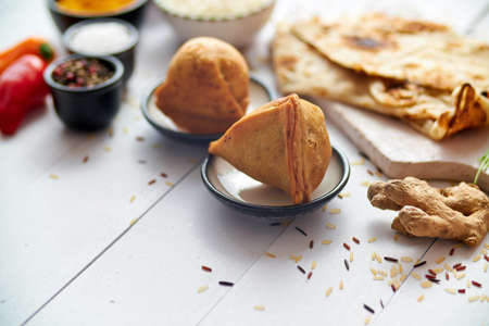 Traditional Indian Food snack Samosa served in a plate on a white wooden table. India food background and texture with copy space Stock Photo