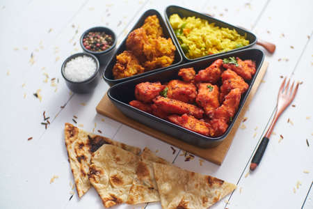 Spicy indian fried chicken served with curry vegetable rice, onion bhajia, naan bread. Placed on white wooden table.