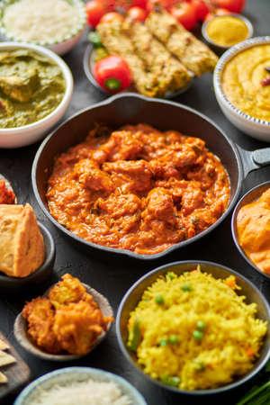 Verschiedene indische Gerichte auf einem Tisch. Würziges Hühnchen Tikka Masala in einer Eisenpfanne. Serviert mit Reis, Naan und Gewürzen. Satz verschiedenes indisches Essen. Standard-Bild