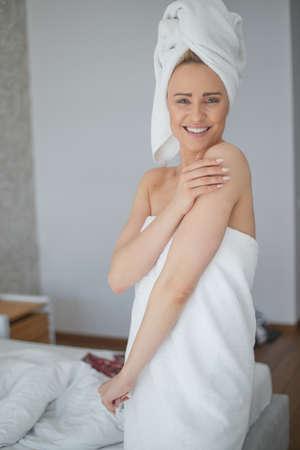 Schöne blonde Frau mittleren Alters befeuchtet Arm nach der Dusche. Verwenden Sie eine organische weiße Creme. Sie ist in Handtücher gewickelt.