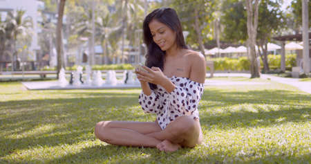 Long haired cheerful Asian woman in fashion swimwear with open shoulders surfing smartphone while sitting with crossed legs in park in Thailand, Phuket