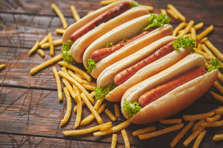 American hot dogs assorted in row. Served with french fries. Placed on wooden table. Above view on a rustic wood background Stock Photo