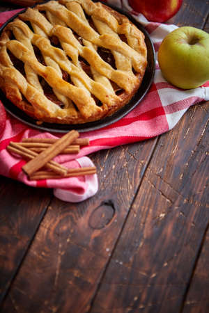 Homemade pastry apple pie with bakery products on dark rusty wooden kitchen table red and green apples and cinnamon. Traditional american dessert. Flat lay food background. Top view Zdjęcie Seryjne