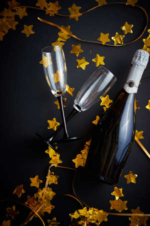 Glasses and bottle of champagne with golden serpentines and confetti lying on black background. New Year or party celebration concept. Top view. Flat lay.
