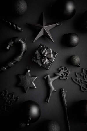 Christmas minimalistic and simple composition in mat black color. Christmas gifts, decorations on black background. Flat lay, top view . 写真素材