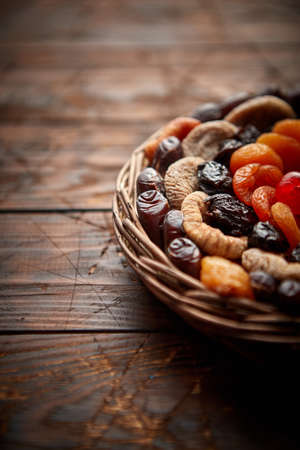 Mix of dried fruits in a small wicker basket on wooden table. Assortment contais apricots, plums, figs, dates, cherries, peaches. Above view with copy space.