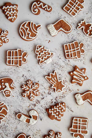 Composition of delicious gingerbread cookies shaped in various Christmas symbols. Placed on white rusty table. Top view.