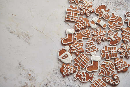Assortment of fresh gingerbread Christmas cookies in various shapes. Placed on white rusty table with copy space.