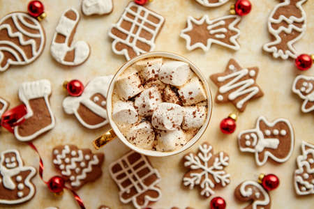 Cup of hot chocolate with tasety marshmellows. Fresh baked Christmas shaped gingerbread cookies on sides. With Xmas decorations. View from above.