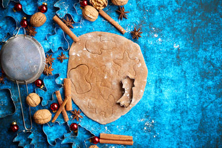 Christmas baking concept. Gingerbread dough with different cutter shapes and spices on sides. Top view on blue rustic background. Imagens