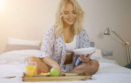 Beautiful young woman in bra and shirt sitting on bed and having good breakfast from tray. Banco de Imagens