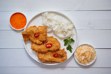 Crispy chicken fried in breadcrumbs served with rice. View from the top on white wooden background. Flat lay.