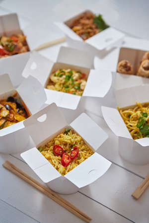 Asian take away or delivery food concept. Paper boxes placed on white wooden table. With various oriental dishes.