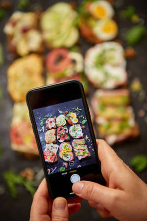 Woman making a photo with a smartphone of assortment of home made sandwiches with various toppings. With colorful fresh vegetables. Healthy food concept. Top view. Black rusty background.