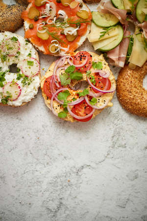 Homemade Bagel sandwiches with different toppings, salmon, cottage cheese, hummus, ham, radish and fresh herbs on a white rusty table, top view. Delicious and healthy breakfast concept.
