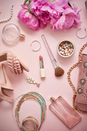 Beauty and fashion accessories and gadgets. Femine concept. Flat lay on pink theme background. With shoes, purse, cosmetics, flower.