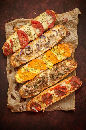 Assortment of various toppings baked sandwiches. With melted cheese, vegetables, tuna, olives and spices. Home fast food composition. Top view. 版權商用圖片
