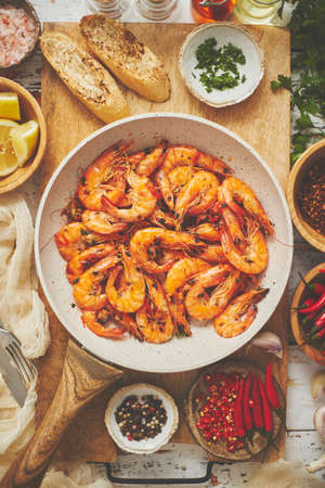 Traditional fried tiger prawn with garlic bread as top view served in a white frying pan. With ingredients on sides. Mediterranean food concept. Top view, flat lay.