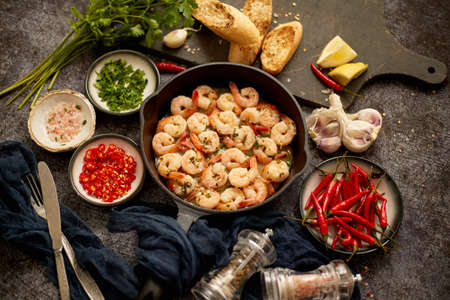 Tasty shrimp tails fried in butter with, garlic, parsley, white wine and chili. With various ingredients on sides. Home seafood concept. Top view, flat lay. Stok Fotoğraf