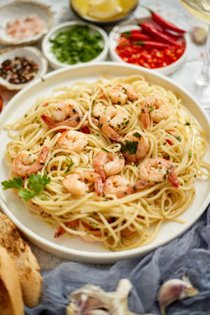 Spaghetti with shrimps on white ceramic plate and served with glass of white wine. Various fresh ingredients on sides. Top view, flat lay.