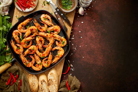 Tasty appetizing roasted shrimps prawns with spices on pan with ingredients on rusty background. Top View with Copy space. Food Background Italian Kitchen Concept