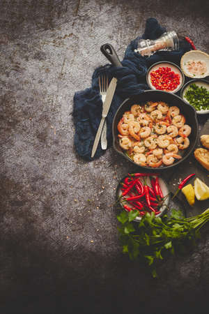 Seafood dinner. Grilled shrimps in cast iron grilling pan with fresh lemon, parsley, chili pepper and garlic white wine sauce over grey concrete background, top view, flat lay with copy space. Reklamní fotografie