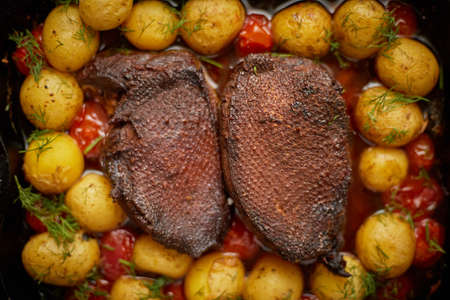 Close up of Roasted Duck or Goose breast. Served with baked potatoes and cherry tomatoes. Top view, flat lay.