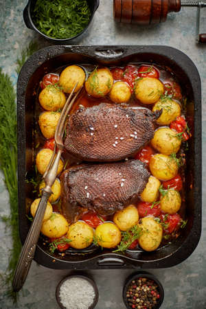 Delicious roasted goose breast served with vegetables, potatoes and dill. Placed in metal baking dish on stone background. Top view flat lay.