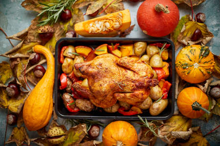 Roasted chicken or turkey garnished with pumpkins, pepper and potatoes. Served on a rustic style table decorated with autumn vegetables, chestnuts and leafs. Thanksgiving Day food concept. Flat lay. Top view