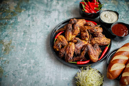 Grilled chicken wings with chilli pepper on a rustic plate served with various dips and bread
