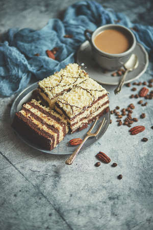 Homemade layered cake sprinkled with white chocolate. Served with cup of coffee on a gray concrete