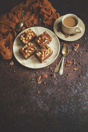 The square pieces of delicious caramel cake with peanuts and brazil nuts served with milk coffee
