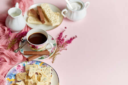 Hot chocolate or cocoa in cup with various sweets on sides. White chocolate bar and biscuits