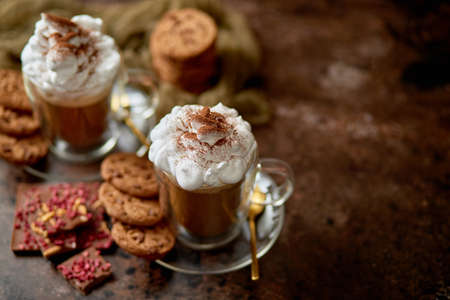 Two tall glasses with hot chocolate, whipped cream and cinnamon powder on top