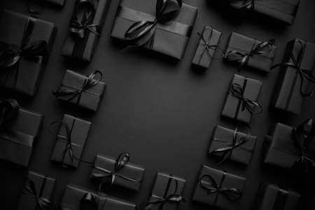 Arranged Gifts boxes wrapped in black paper with black ribbon on black background. Christmas concept Banco de Imagens