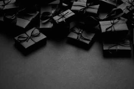 A pile various size black boxed gifts placed on stack. Christmas concept.