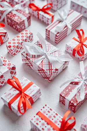 Colorful white and red Christmas theme. Wrapped gifts in festive paper with ribbon Banco de Imagens