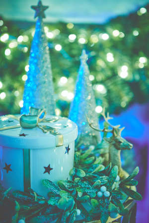 Colorful christmas ornaments and decorations placed on small table with lights in background Banco de Imagens