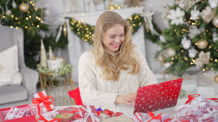 Young pretty blond woman shopping online using laptop against Christmas background Banco de Imagens